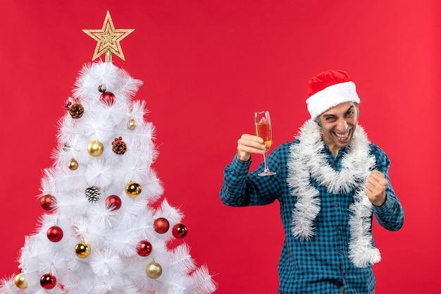 Świąteczny nastrój z dumnym, emocjonalnym młodzieńcem z czapką świętego mikołaja w niebieskiej koszuli w paski, trzymając kieliszek wina w pobliżu choinki