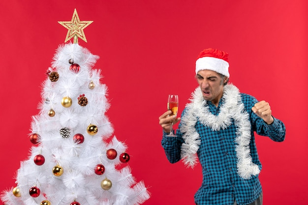 Świąteczny nastrój z dumnym młodym mężczyzną w czapce świętego mikołaja w niebieskiej koszuli w paski, podnoszącym kieliszek wina, pokazując swoje szczęście w pobliżu choinki