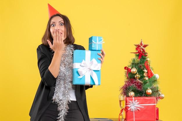 Świąteczny nastrój z emocjonalną piękną damą w kapeluszu xsmas trzymającą prezenty i wykonującą gest ciszy w biurze na żółto