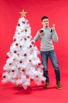 Świąteczny nastrój z emocjonalnym facetem stojącym w pobliżu udekorowanej choinki i dumnym z siebie trzymającym mikrofon i telefon