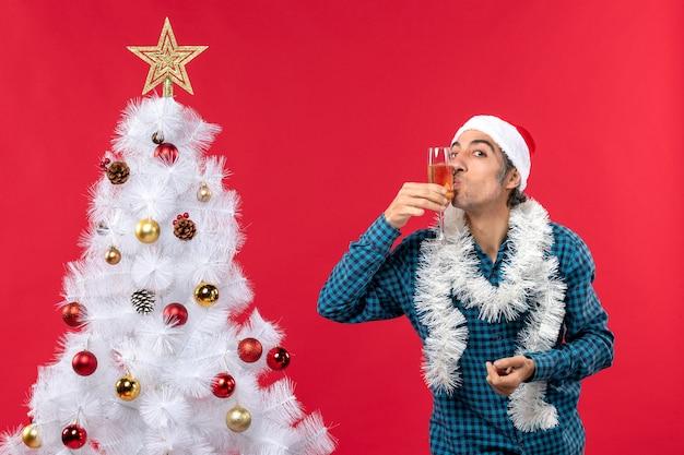 Świąteczny nastrój z emocjonalnym młodym człowiekiem w kapeluszu świętego mikołaja w niebieskiej koszuli w paski, trzymając i całując szkło z winem w pobliżu choinki