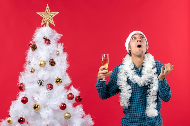 Świąteczny nastrój z emocjonalnym młodym człowiekiem w kapeluszu świętego mikołaja w niebieskiej koszuli z paskiem, trzymając kieliszek wina, patrząc w górę w pobliżu choinki