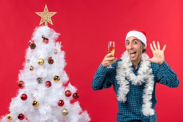 Świąteczny nastrój z emocjonalnym młodym mężczyzną w czapce świętego mikołaja w niebieskiej koszuli w paski, trzymając kieliszek wina i pokazując pięć w pobliżu choinki