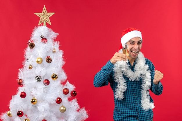 Świąteczny nastrój z emocjonalnym młodzieńcem w kapeluszu świętego mikołaja w niebieskiej koszuli w paski, podnosząc kieliszek wina w pobliżu choinki