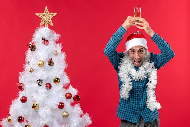 Świąteczny nastrój z emocjonalnym młodzieńcem w kapeluszu świętego mikołaja w niebieskiej koszuli w paski, podnosząc kieliszek wina