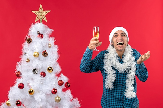 Świąteczny nastrój z emocjonalnym młodzieńcem w kapeluszu świętego mikołaja w niebieskiej koszuli w paski, trzymając kieliszek wina i śmiejąc się w pobliżu choinki