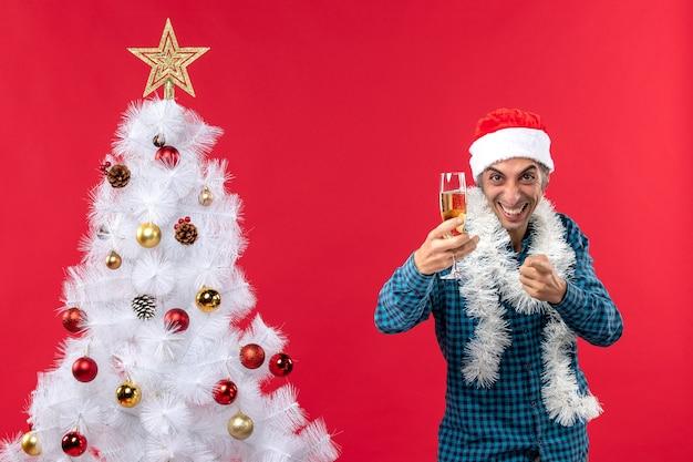 Świąteczny nastrój z emocjonalnym młodzieńcem w kapeluszu świętego mikołaja w niebieskiej koszuli z paskiem, trzymając kieliszek wina, wskazując coś w pobliżu choinki