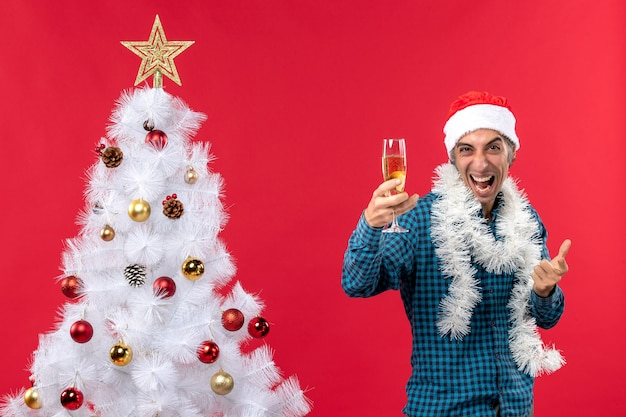 Świąteczny nastrój z emocjonalnym szalonym młodym człowiekiem z czapką świętego mikołaja w niebieskiej koszuli w paski, trzymając kieliszek wina w pobliżu choinki