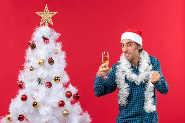 Świąteczny nastrój z emocjonalnym zabawnym młodym mężczyzną z czapką świętego mikołaja w niebieskiej koszuli w paski trzymający kieliszek wina patrząc w górę w pobliżu choinki