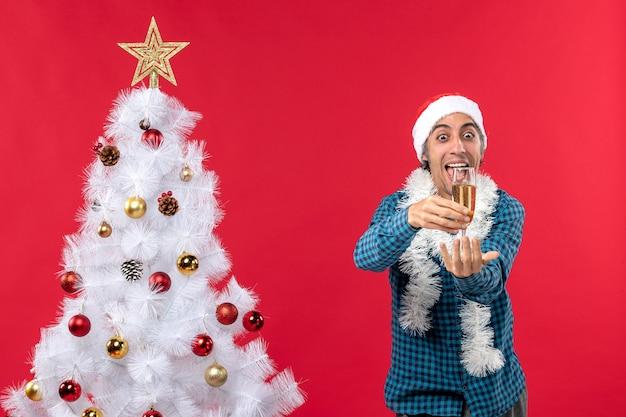 Świąteczny nastrój z emocjonalnym zabawnym młodzieńcem z czapką świętego mikołaja w niebieskiej koszuli w paski, podnosząc kieliszek wina w pobliżu choinki