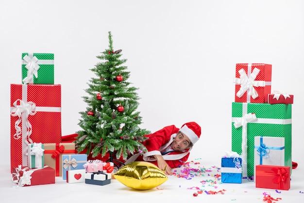 Świąteczny nastrój z mikołajem leżącym za choinką w pobliżu prezentów w różnych kolorach na białym tle