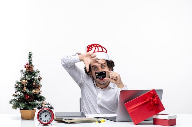 Świąteczny nastrój z młodą brodatą zaskoczoną pozytywną biznesmenką w kapeluszu świętego mikołaja i trzymającą kartę bankową na białym tle