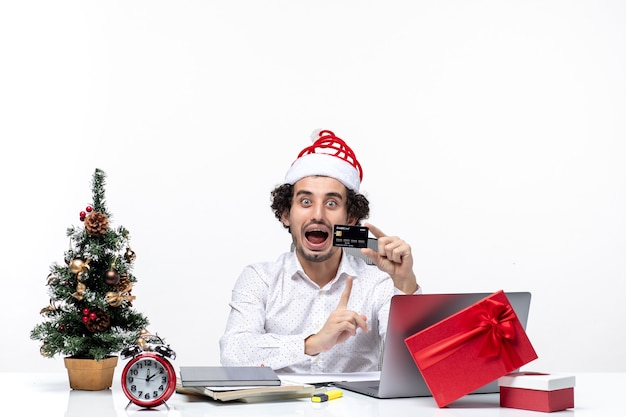 Świąteczny nastrój z młodą brodatą zaskoczoną pozytywną biznesmenką z czapką świętego mikołaja i wskazującą kartą bankową na białym tle