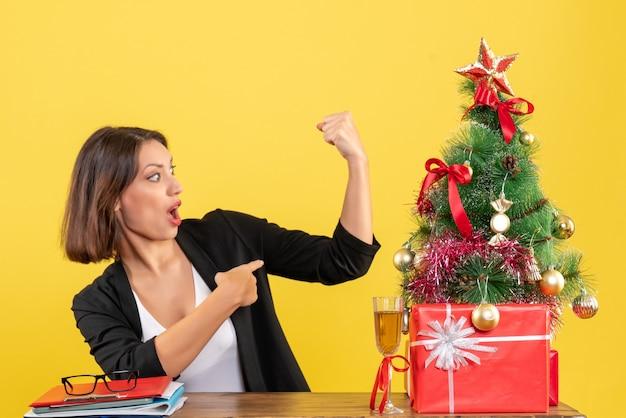 Świąteczny nastrój z młodą dumną biznesową damą pokazującą swoją siłę na żółto