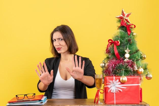 Świąteczny nastrój z młodą niezadowoloną emocjonalną kobietą biznesu pokazującą dziesięć na żółto