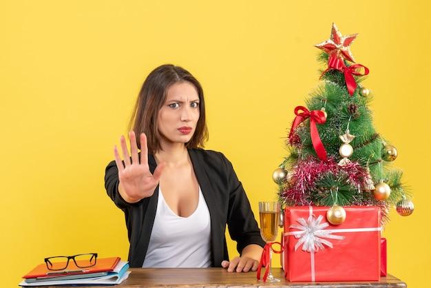 Świąteczny nastrój z młodą niezadowoloną, poważną, emocjonalną kobietą biznesu pokazującą pięć na żółto