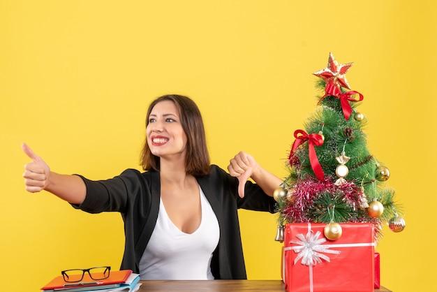Świąteczny nastrój z młodą piękną kobietą siedzącą przy stole w biurze