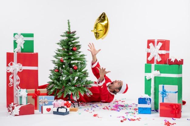 Świąteczny nastrój z młodym mikołajem leżącym za choinką w pobliżu prezentów w różnych kolorach na białym tle
