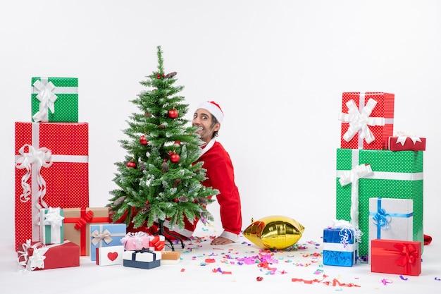Świąteczny nastrój z młodym pozytywnym zabawnym mikołajem leżącym za choinką w pobliżu prezentów w różnych kolorach na białym tle