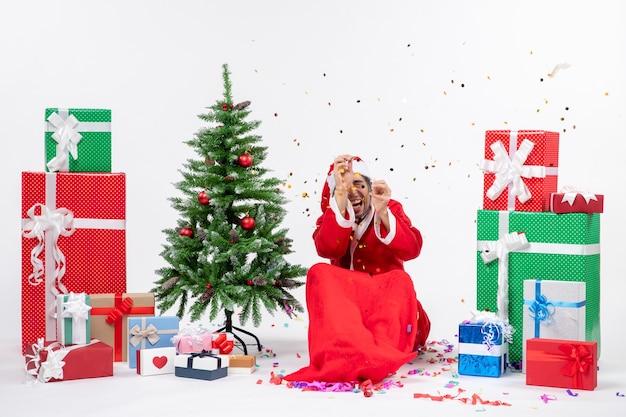 Świąteczny nastrój z młodym przerażonym mikołajem siedzącym w pobliżu choinki i prezentów w różnych kolorach na białym tle