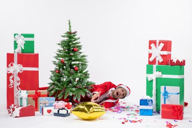 Świąteczny nastrój z młodym smutnym mikołajem leżącym za choinką w pobliżu prezentów w różnych kolorach na białym tle