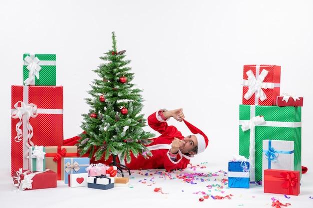 Świąteczny nastrój z młodym zabawnym mikołajem leżącym za choinką w pobliżu prezentów na białym tle