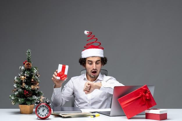 Świąteczny nastrój z nerwowym młodym biznesmenem w kapeluszu świętego mikołaja, trzymając prezent i sprawdzając swój czas na ciemnym tle