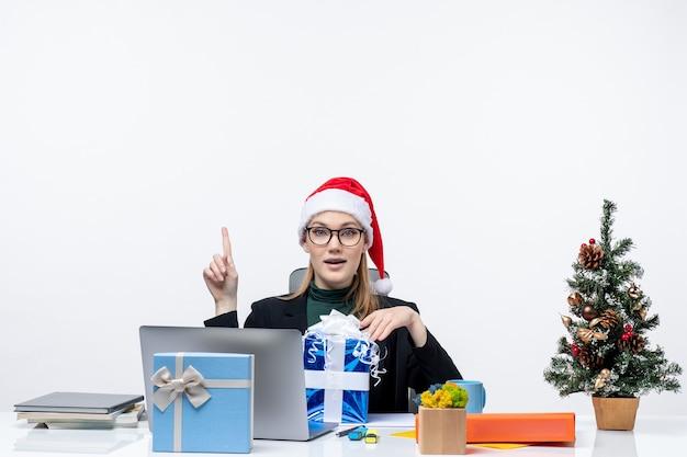 Świąteczny nastrój z pewną siebie młodą kobietą w czapce świętego mikołaja i noszących okulary siedzącą przy stole z prezentem i pokazującą powyżej na białym tle