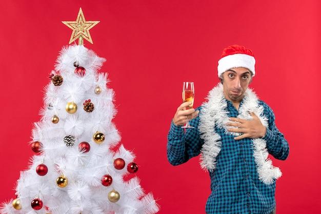 Świąteczny nastrój z pewnym siebie młodym człowiekiem w kapeluszu świętego mikołaja w niebieskiej koszuli z paskiem, trzymając kieliszek wina w pobliżu choinki
