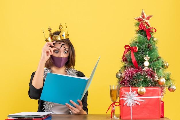 Świąteczny nastrój z piękną damą w garniturze w koronie z maską medyczną czytającą dokumenty w biurze na żółto