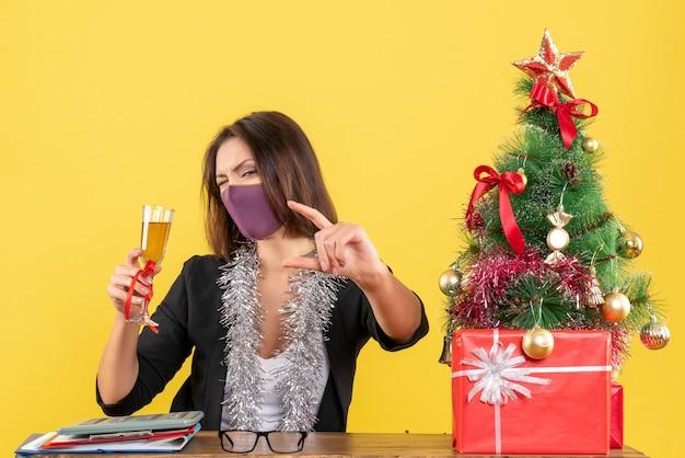Świąteczny nastrój z piękną damą w garniturze w masce medycznej i podnoszącą wino w biurze na żółto