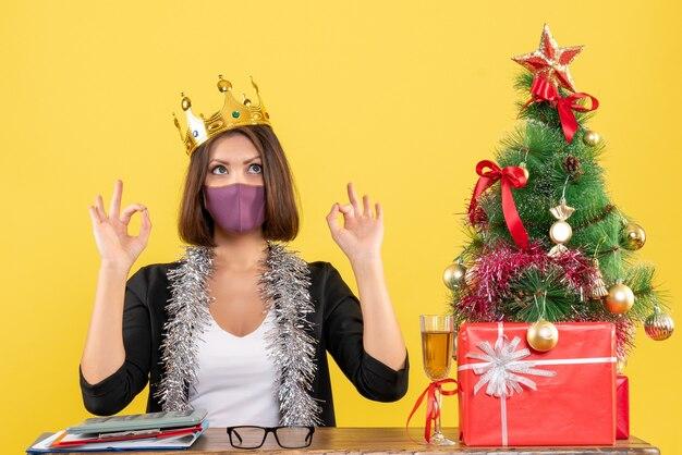 Świąteczny nastrój z piękną damą w garniturze z maską medyczną i noszącą maskę wykonującą gest okularów w biurze na żółto