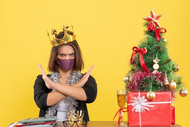 Świąteczny nastrój z piękną damą w garniturze z maską medyczną i noszącą maskę wykonującą negatywny gest w biurze na żółto
