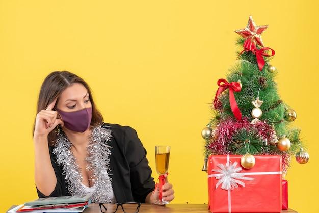 Świąteczny nastrój z piękną damą w garniturze z maską medyczną i podnoszącą wino w biurze na żółto