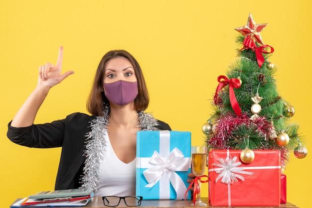Świąteczny nastrój z piękną damą w garniturze z maską medyczną i prezentem trzymającym skierowaną w górę w biurze na żółto