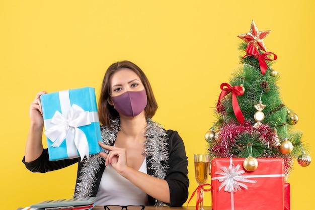 Świąteczny nastrój z piękną damą w garniturze z maską medyczną i prezentem trzymającym w biurze na żółto