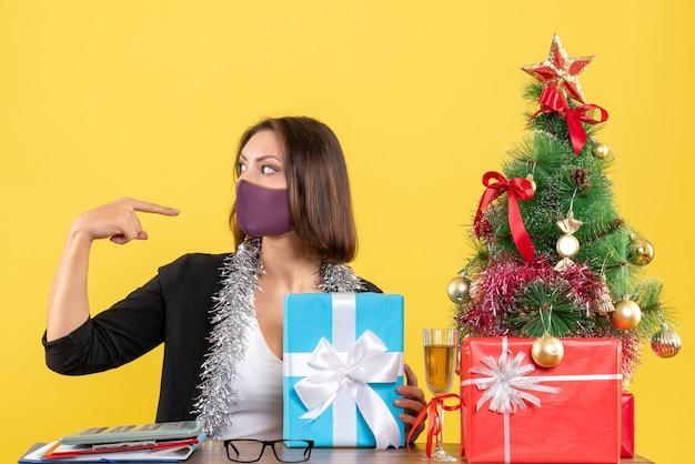 Świąteczny nastrój z piękną damą w garniturze z maską medyczną i prezentem trzymającym wskazującą się w biurze na żółto