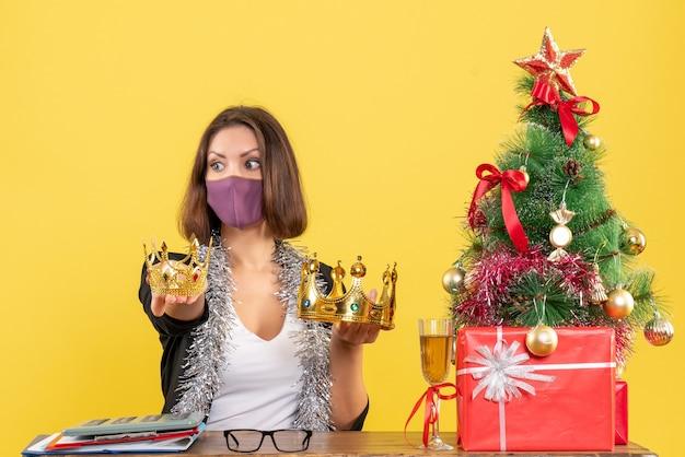 Świąteczny nastrój z piękną damą w garniturze z maską medyczną i trzymającą korony w biurze na żółto