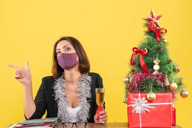 Świąteczny nastrój z piękną damą w garniturze z maską medyczną i trzymającą wino w biurze na żółto