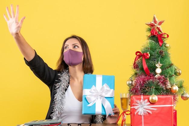 Świąteczny nastrój z piękną damą w garniturze z maską medyczną i trzymającym prezent witający się w biurze na żółto