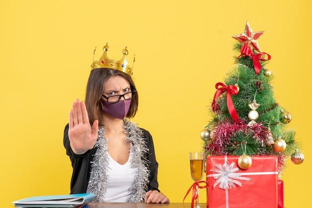 Świąteczny nastrój z piękną damą w garniturze z noszącą koronę z jej medyczną maską wykonującą gest stopu w biurze na żółto