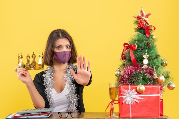 Świąteczny nastrój z piękną damą w garniturze z trzymającą koroną w jej masce medycznej wykonującej gest stopu w biurze na żółto