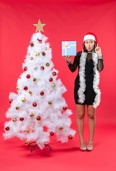 Świąteczny nastrój z piękną, przemyślną dziewczyną w czarnej sukience z czapką mikołaja stojącą w pobliżu choinki i trzymającą noworoczny prezent