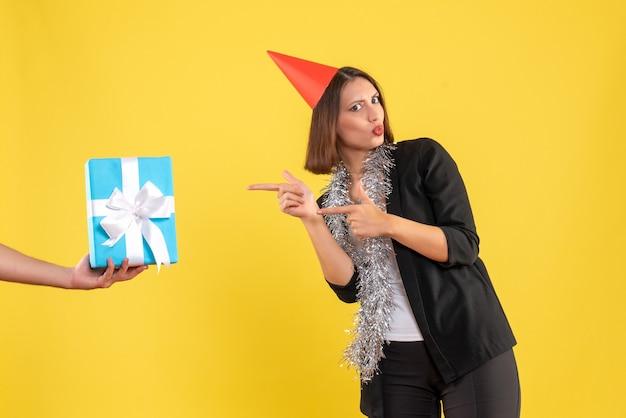 Świąteczny nastrój z podekscytowaną biznesową damą w garniturze z kapeluszem xsmas, wskazując dłoń trzymającą prezent na żółto