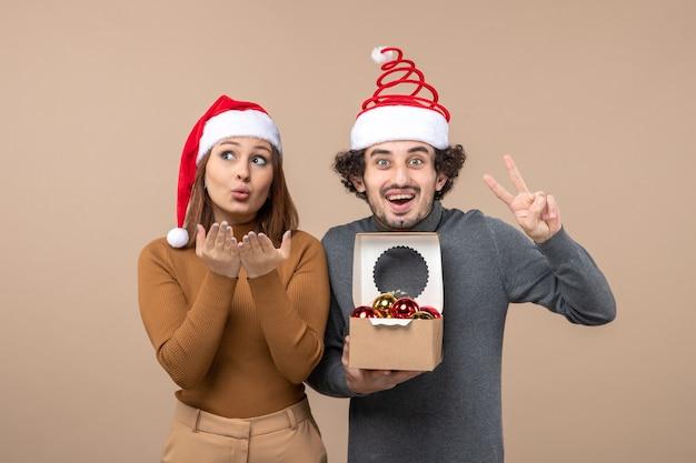 Świąteczny nastrój z podekscytowaną uroczą chłodną parą w czerwonych czapkach świętego mikołaja