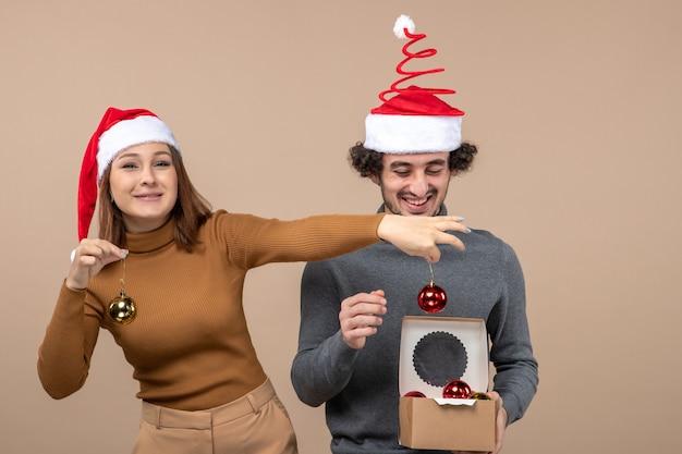Świąteczny nastrój z podekscytowaną uroczą parą w czerwonych czapkach świętego mikołaja otwierającą akcesoria dekoracyjne na szaro