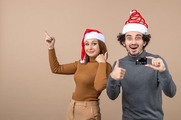 Świąteczny nastrój z podekscytowanym zadowolony fajna para ubrana w czerwone czapki świętego mikołaja facet pokazujący kartę bankową, kobieta wskazująca powyżej obu robi doskonały gest