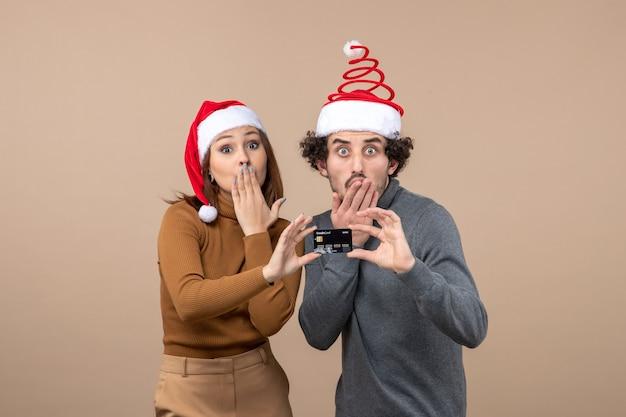 Świąteczny nastrój z podekscytowanym zszokowanym chłodnym parą w czerwonych czapkach świętego mikołaja pokazując kartę bankową