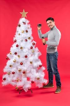 Świąteczny nastrój z poważnym młodym facetem stojącym w pobliżu udekorowanej choinki i trzymając mikrofon, robienie zdjęć