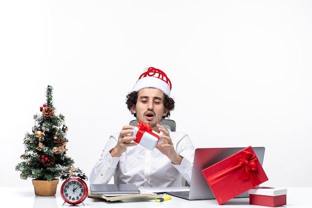 Świąteczny nastrój z poważnym zapracowanym biznesmenem w kapeluszu świętego mikołaja podnoszącym prezent i patrząc na niego na białym tle